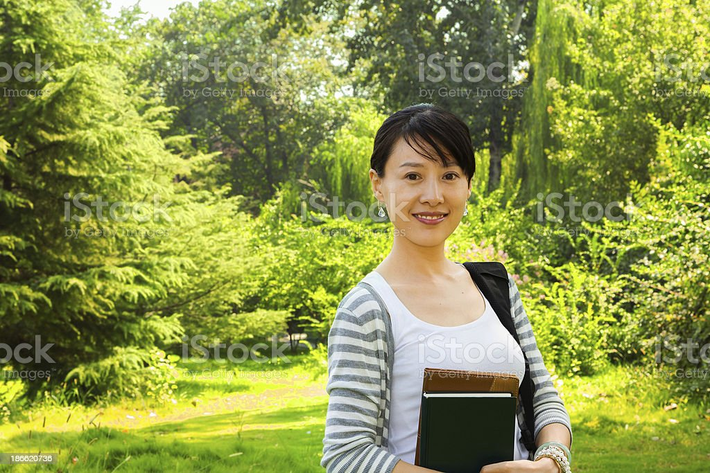 Asian Female Student holding book in Campus royalty-free stock photo