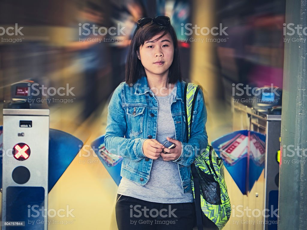 Asian female student passing through railway station entry barriers stock photo