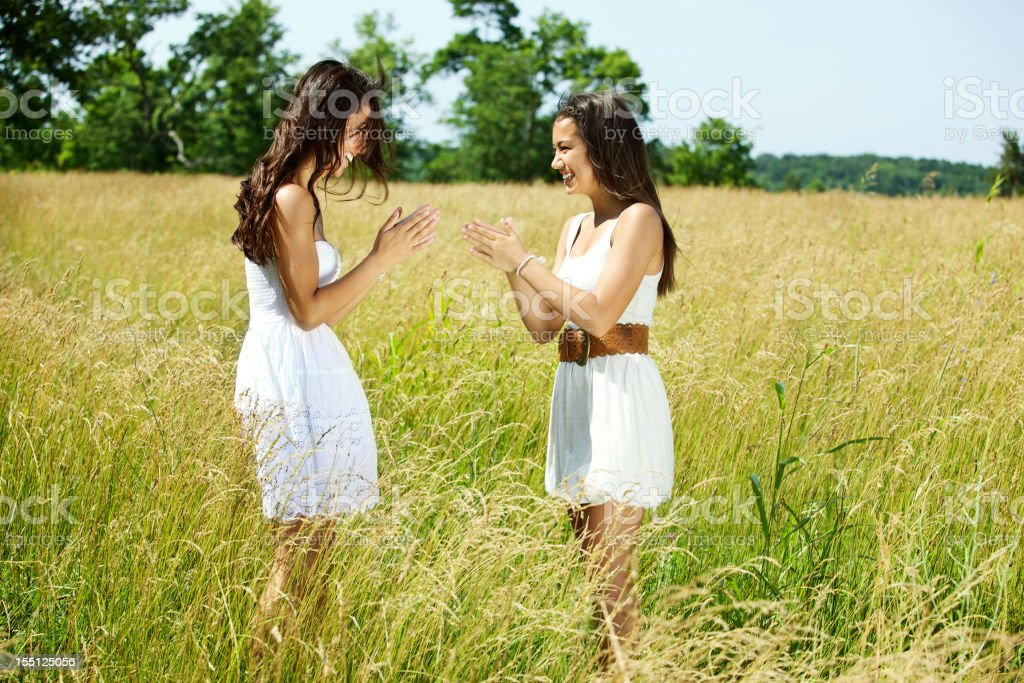 asian female teens in grassy summer field stock photo