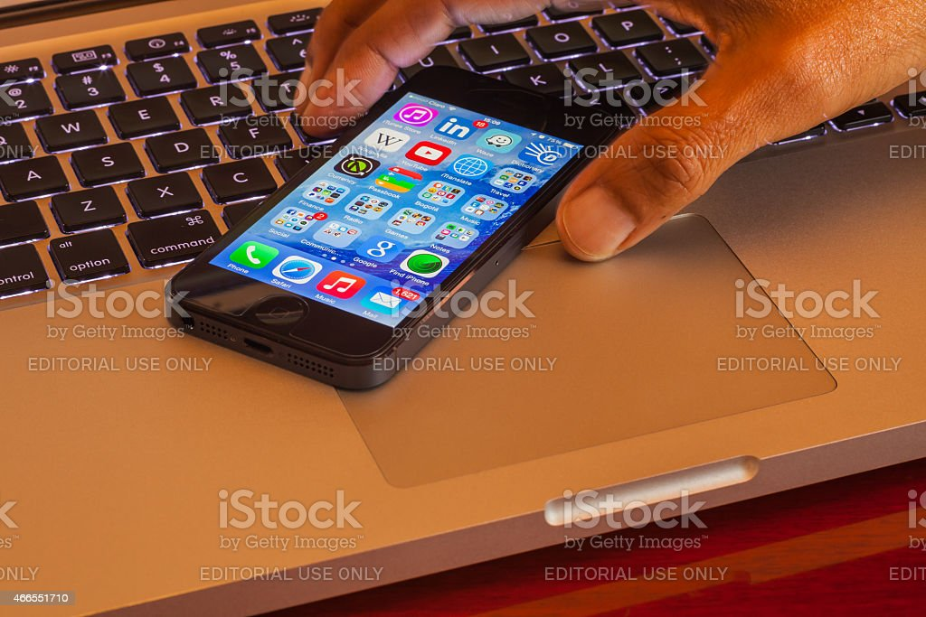 Asian fingers picking up iPhone5 from computer keyboard; studio shot stock photo