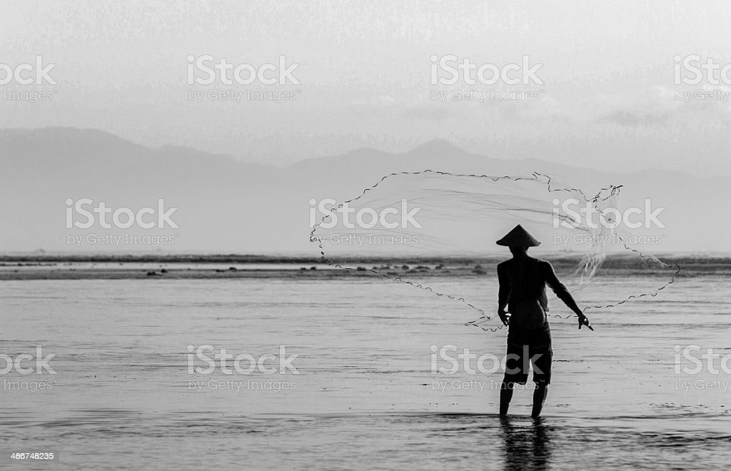 Asian fisherman throwing his fishnet stock photo