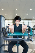 Asian fit man playing arm curl workout at fitness gym.