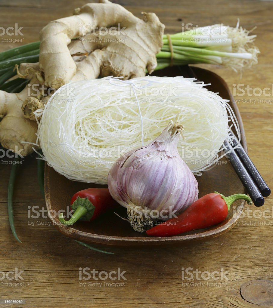 Asian food ingredients - rice noodles, ginger, chili pepper, garlic royalty-free stock photo