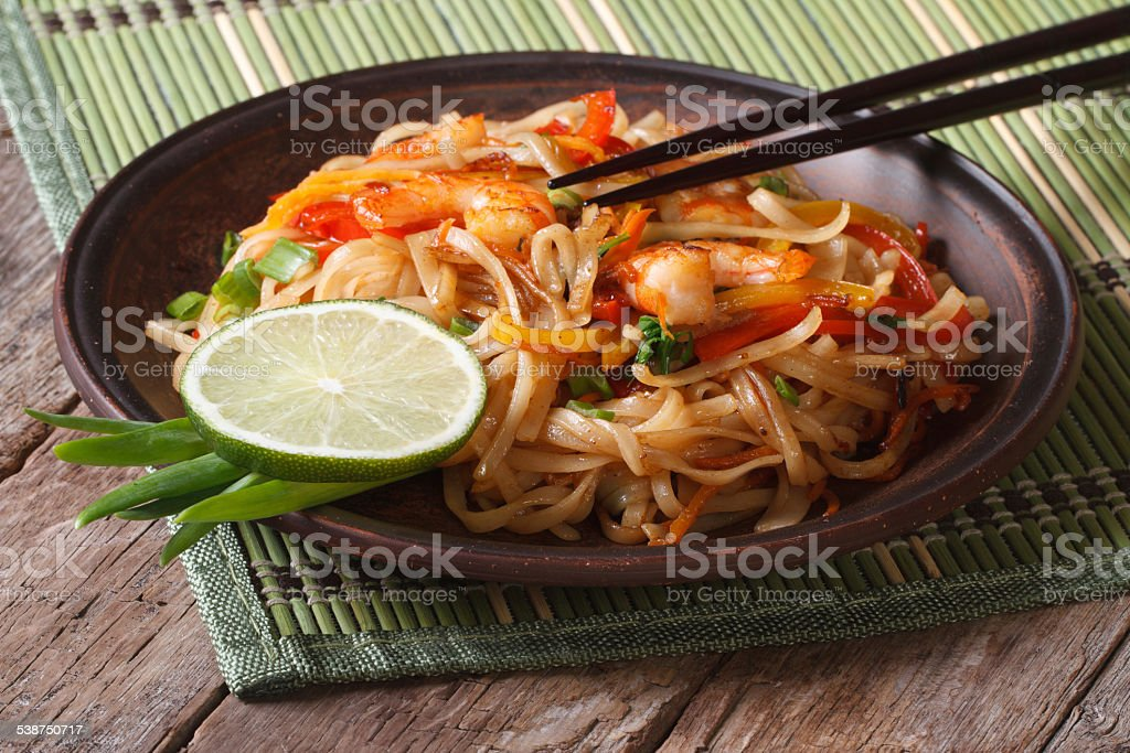Asian food: rice noodles with shrimp and vegetables stock photo