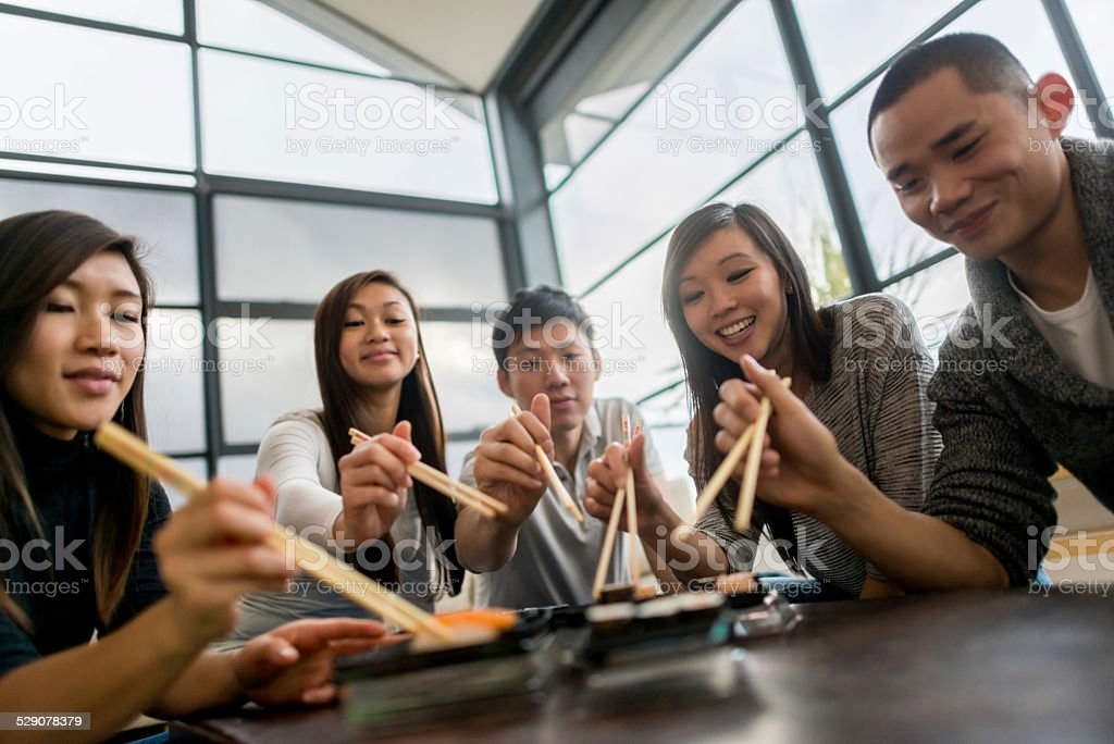 Asian friends eating sushi stock photo