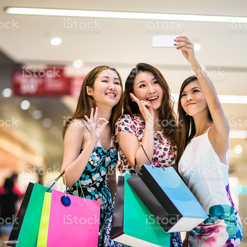 asian friends shopping in the mall and take a selfie stock photo