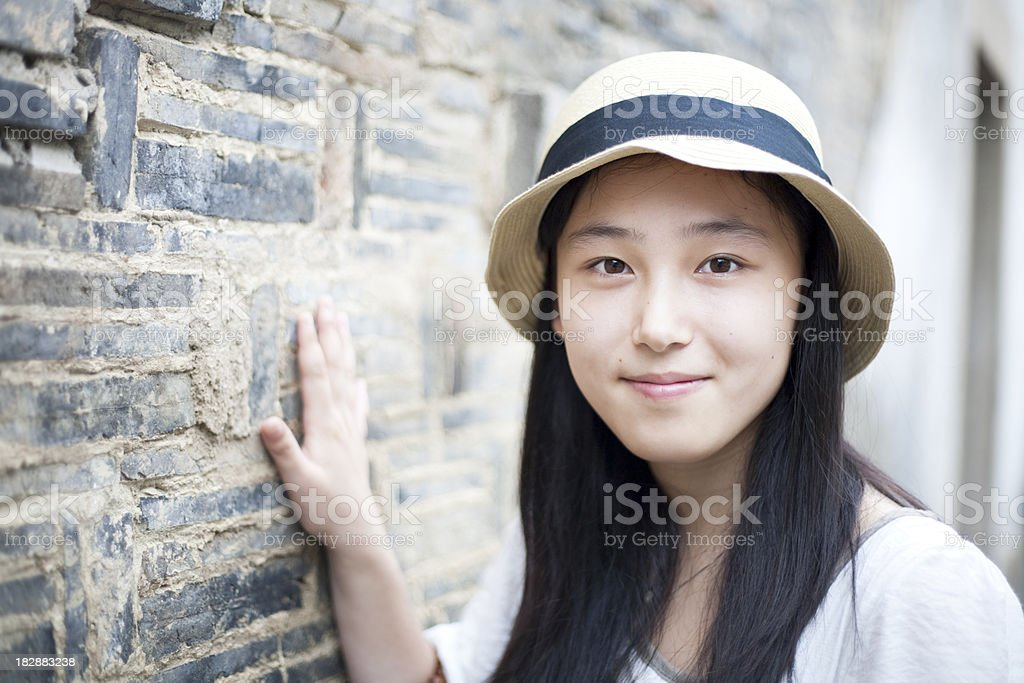 Asian girl and old brick wall royalty-free stock photo