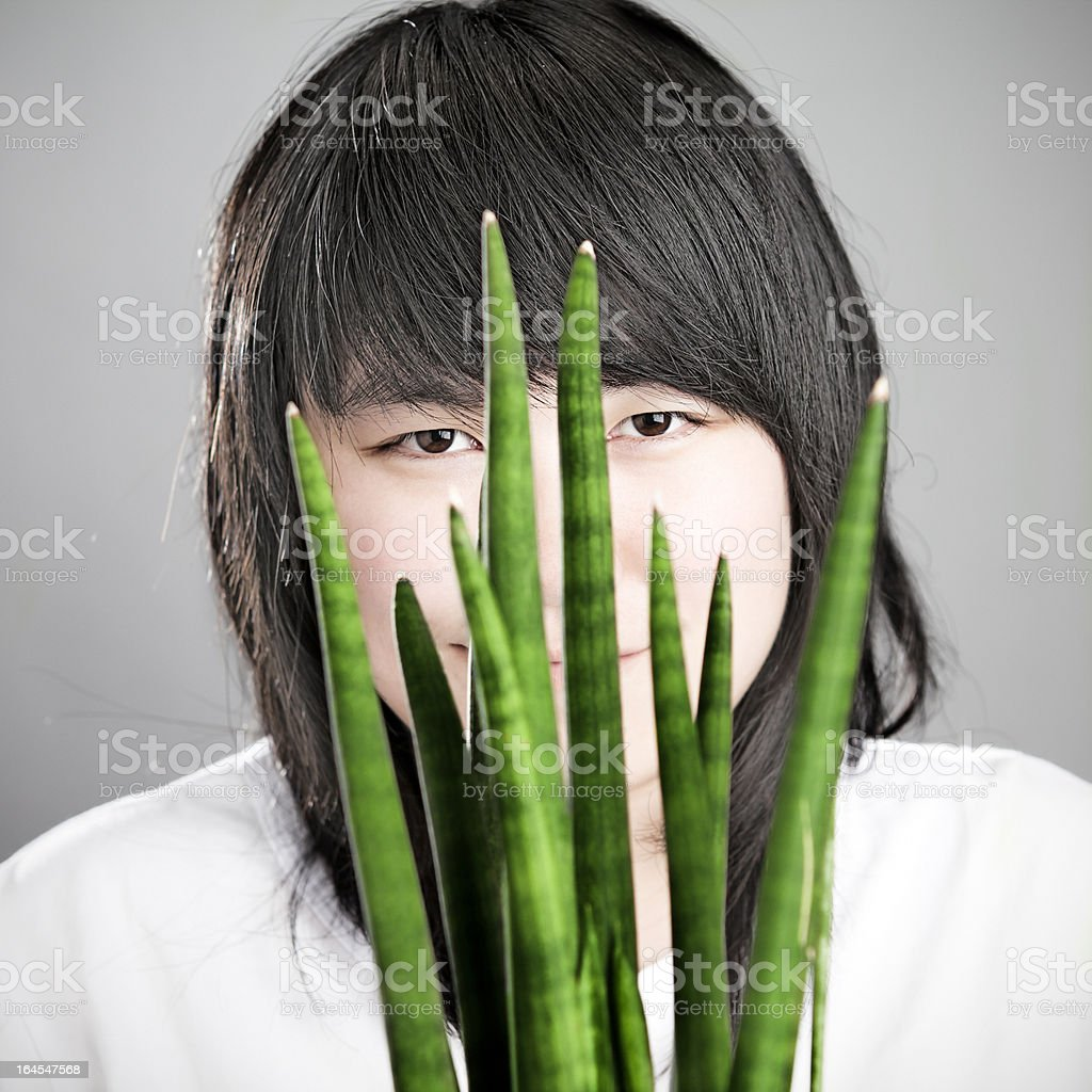Asian girl behind a Sansevieria Cylindrica stock photo