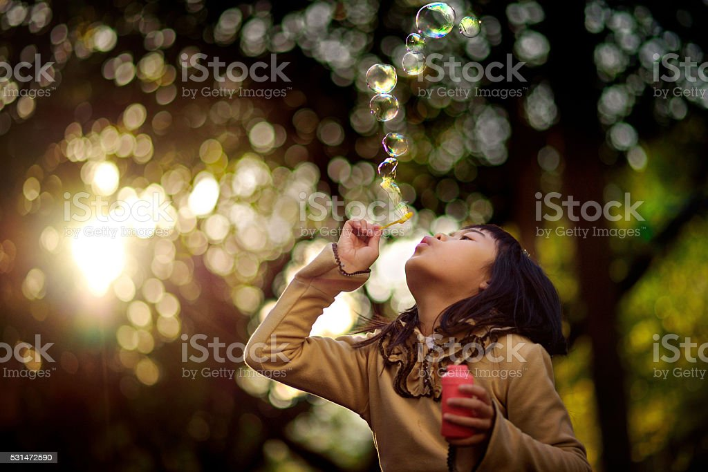 Asian girl blowing bubbles stock photo