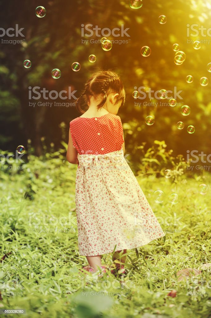 Asian girl catches soap bubbles on nature background. Back view. stock photo