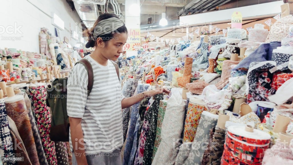Asian girl choose items in a fabric shop, Thailand. stock photo