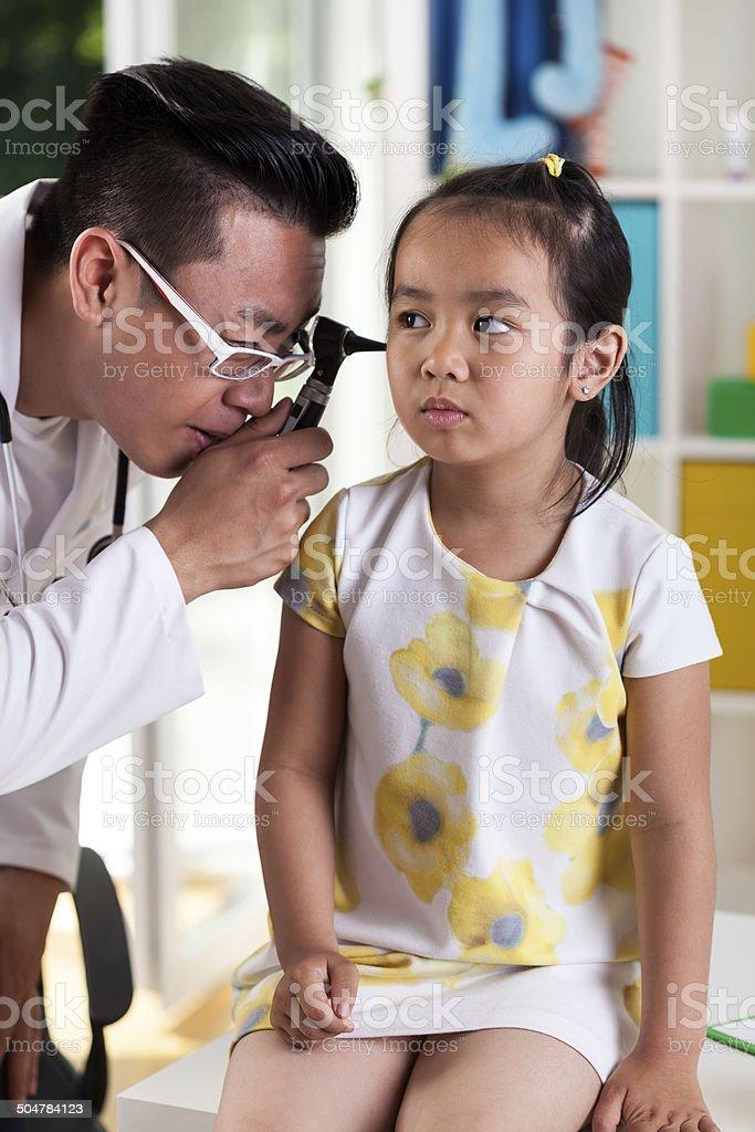 Asian girl during ear examination stock photo