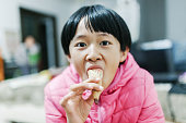 asian girl eating ice cream cone at home