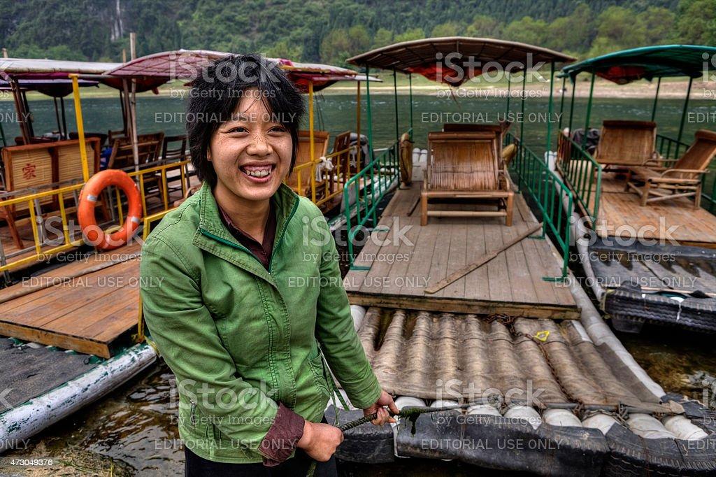 Asian girl ferryman moors bamboo raft, and smiles, Guangxi, China stock photo