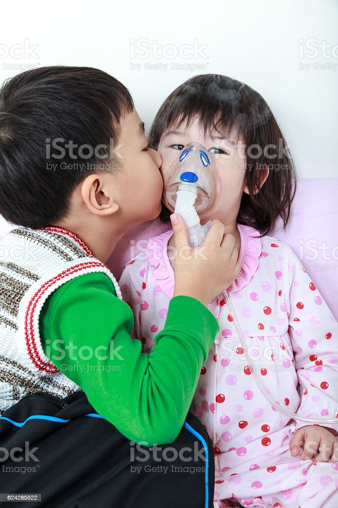 Asian girl having respiratory illness helped by brother with inh stock photo