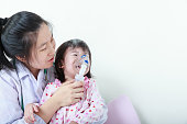 Asian girl having respiratory illness helped by health professio