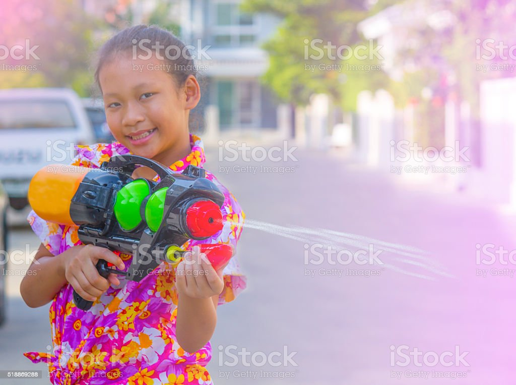 Asian girl holding a plastic water gun festival in Thailand . stock photo