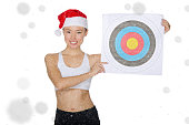 Asian girl holding target in snow