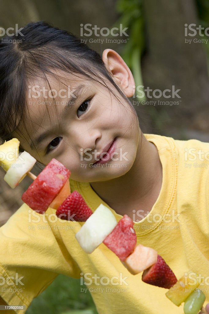 Asian girl holding up fruit skewer royalty-free stock photo