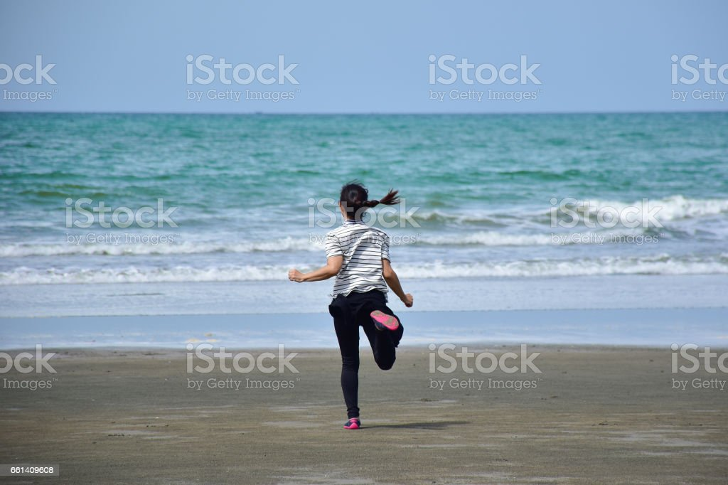 asian girl is running on the beach into the sea, excited, sad,...