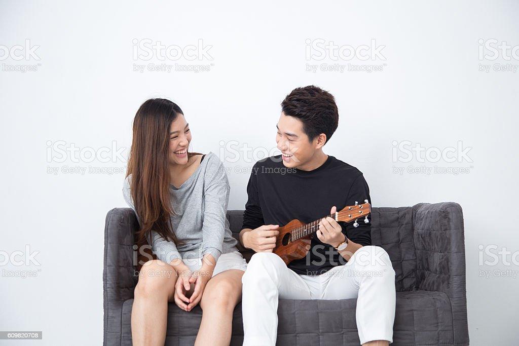 Asian girl listening to Asian boy play ukulele stock photo