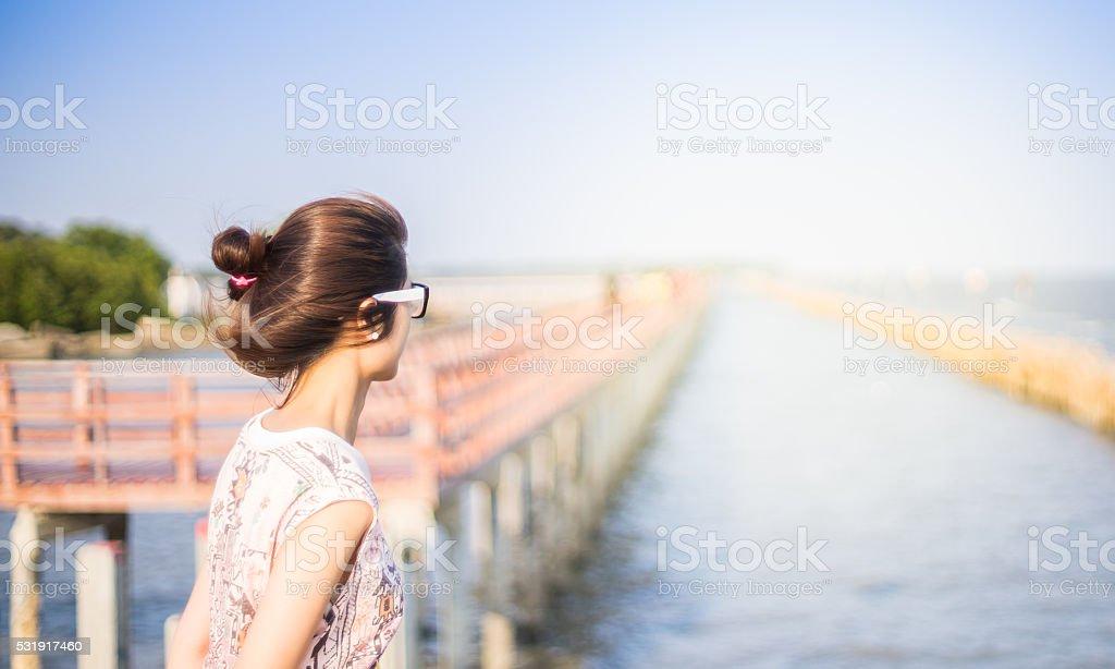 Asian Girl looking at wide ocean beach stock photo