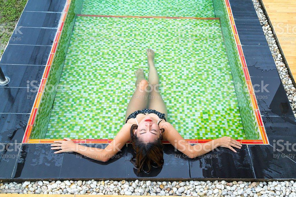 Asiatique fille allongé au bord de la piscine photo libre de droits