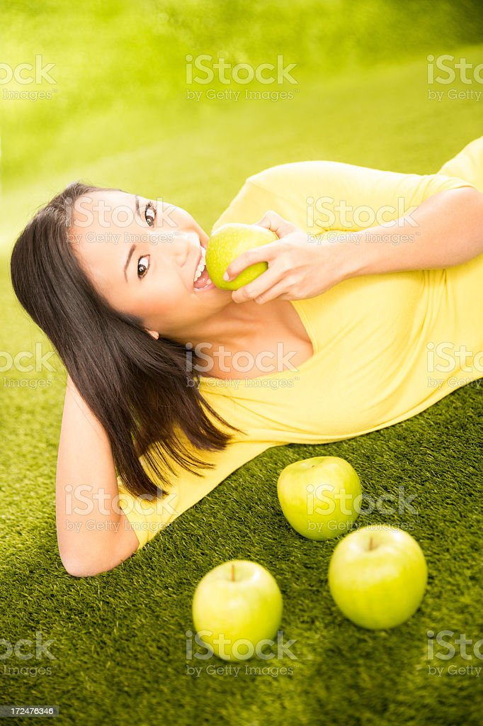 Asian girl lying on grass in park eating an apple royalty-free stock photo