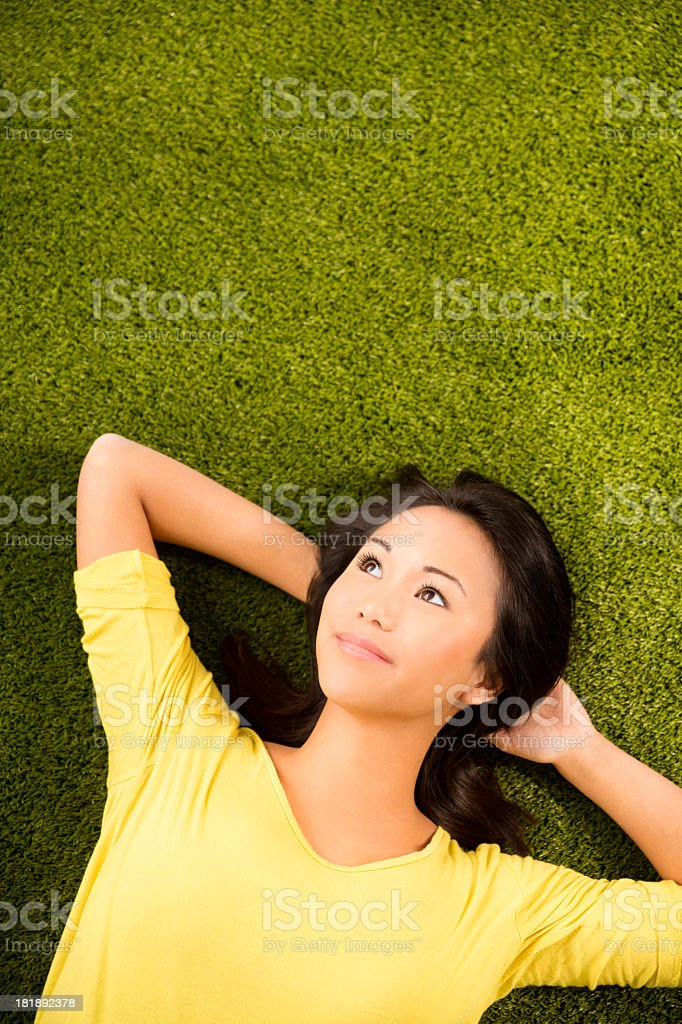 Asian girl lying on grass looking at copy space royalty-free stock photo