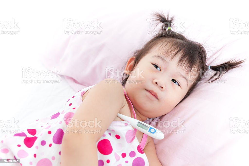 Asian girl lying on sickbed with digital thermometer stock photo