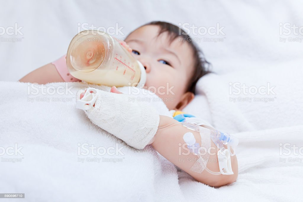 Asian girl lying with saline intravenous (IV) on hand. stock photo