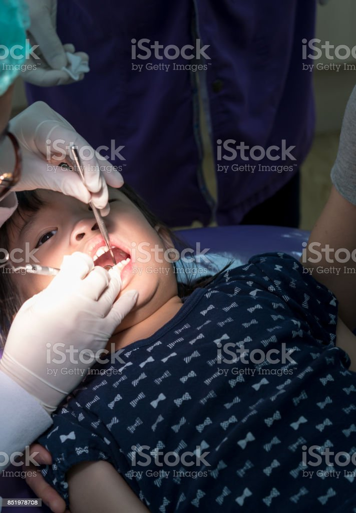 Asian girl met the dentist for routine dental checkup and fluoride treatment. stock photo