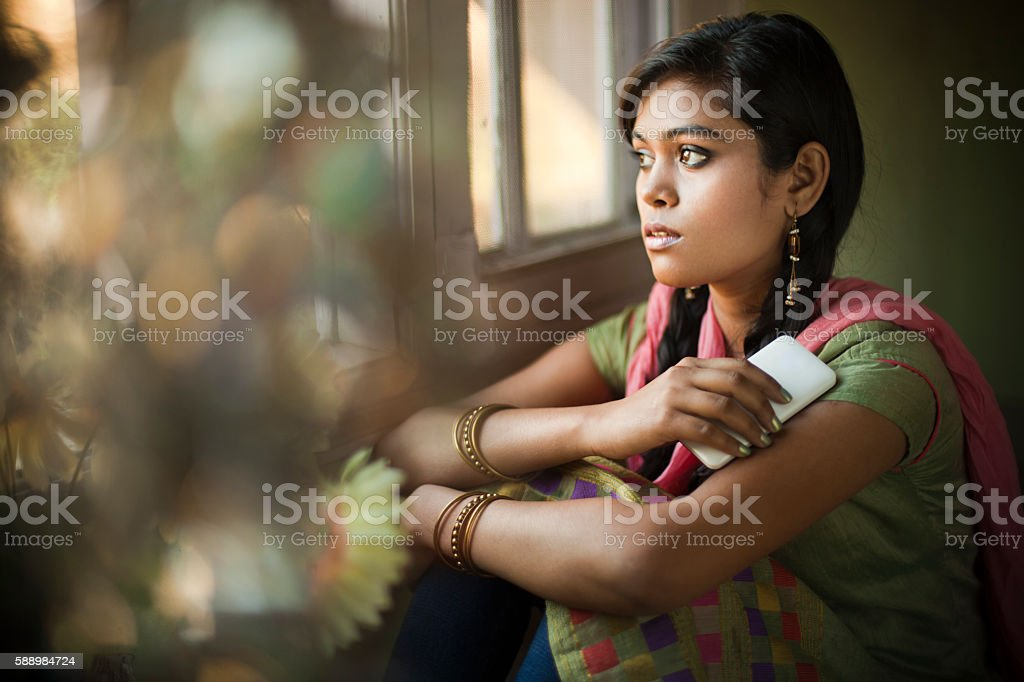 Asian girl next to window with mobile phone looking away. stock photo