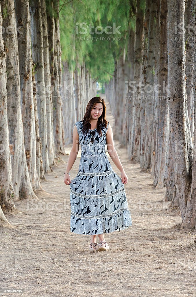 asian girl on the road pine trees stock photo