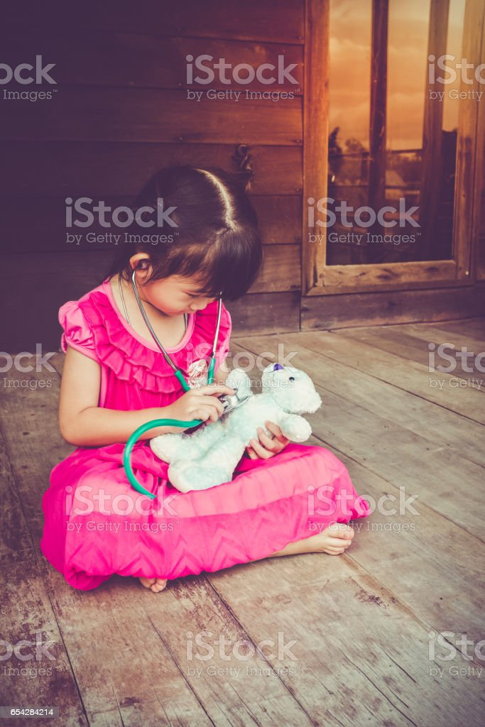 Asian girl playing doctor with plush toy bear at home. stock photo