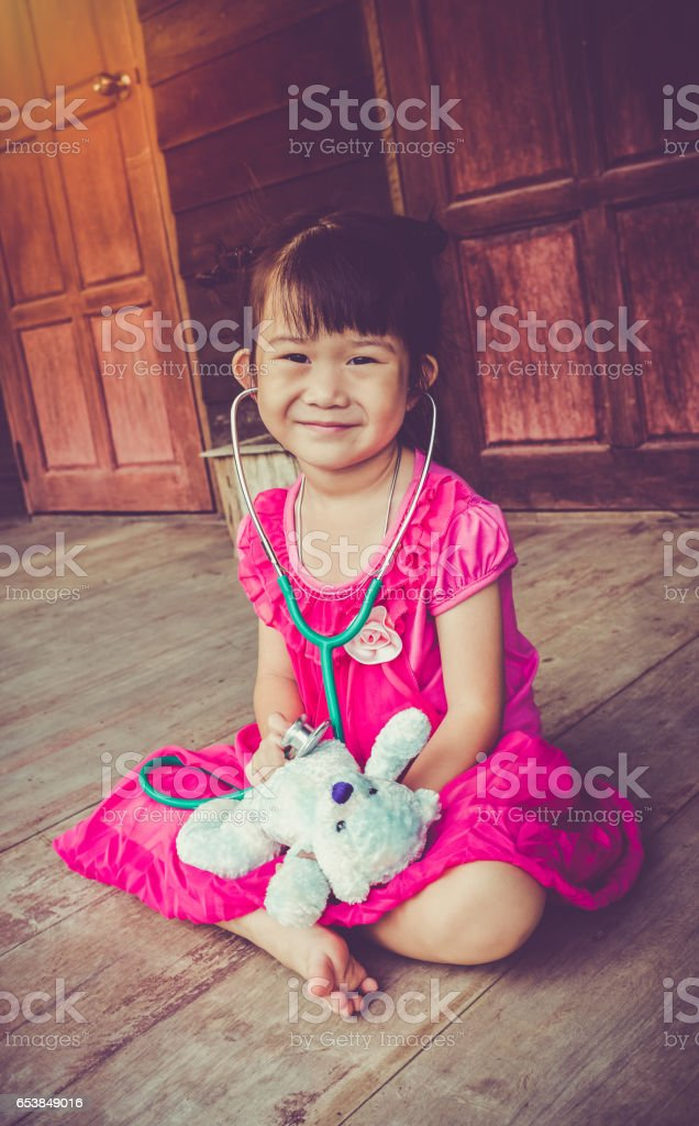 Asian girl playing doctor with plush toy bear. Vintage tone. stock photo