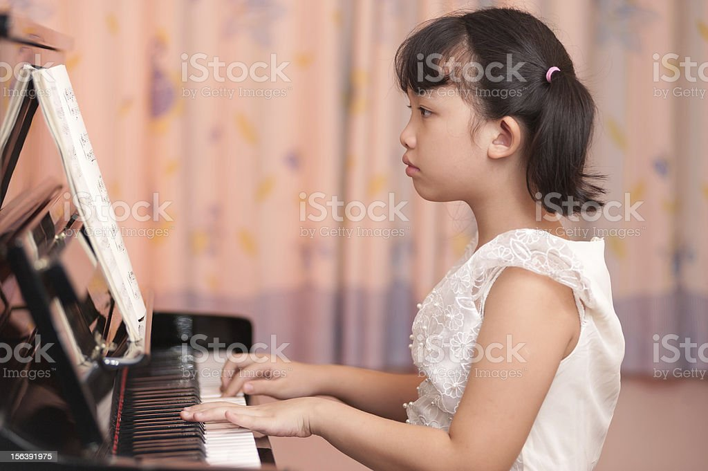 Asian girl playing piano royalty-free stock photo