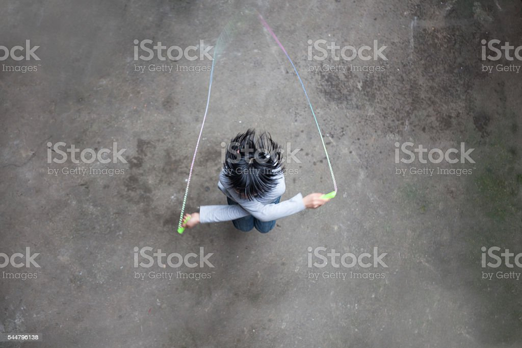 asian girl playing rope skipping stock photo