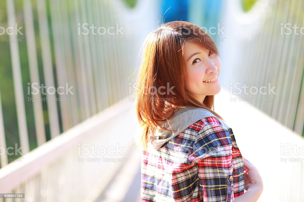 asian girl posing outdoors wear plaid shirt white bridge park stock photo