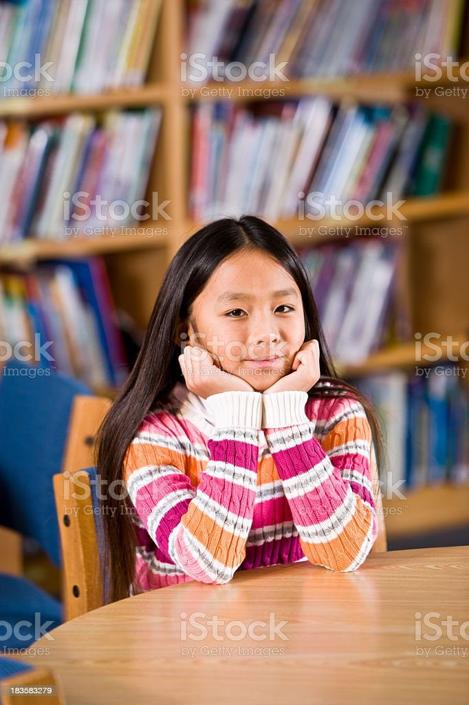 Asian girl sitting in school library royalty-free stock photo