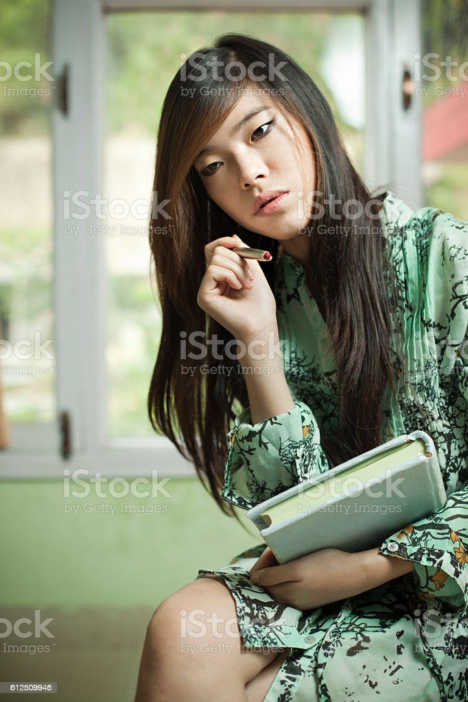 Asian girl student with book and pen looking down. stock photo