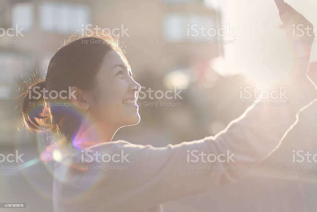 Asian Girl Taking Self Portrait on Cell Phone, Sunny Day royalty-free stock photo