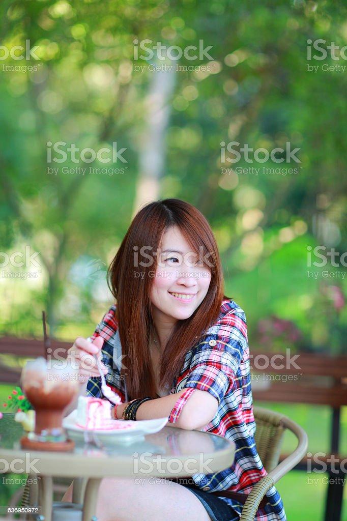 asian girl wear plaid shirt sitting eating cake tea garden stock photo
