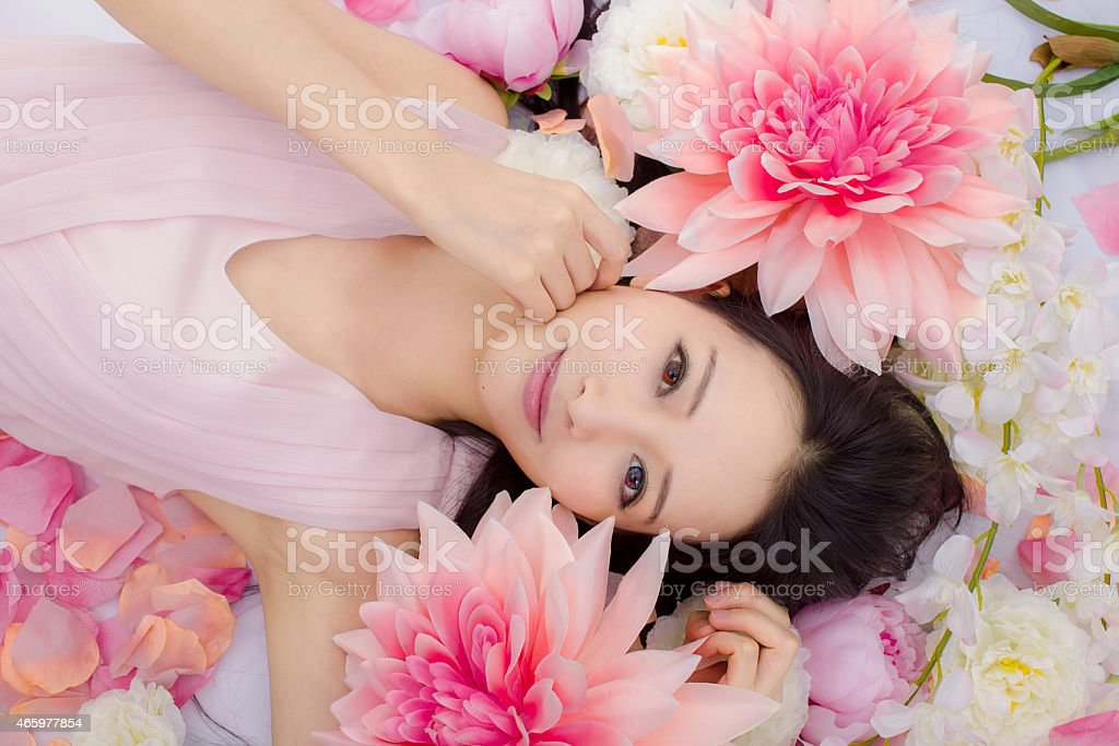 Asian girl with pink shirt lying in a bed of pink flowers stock photo