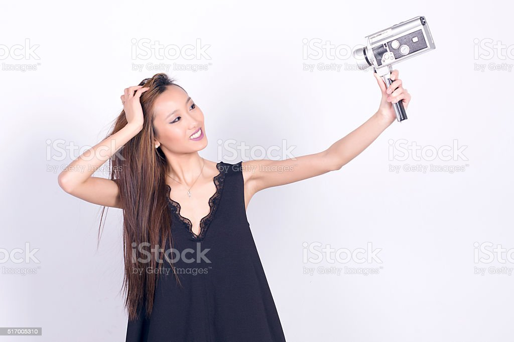 Asian girl with super 8 mm camera, taking selfie. stock photo