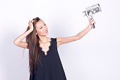 Asian girl with super 8 mm camera, taking selfie.