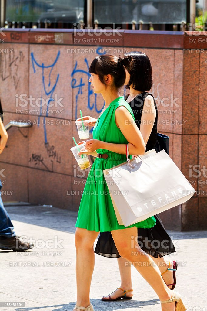 Asian girls with shopping bags and iced coffee stock photo