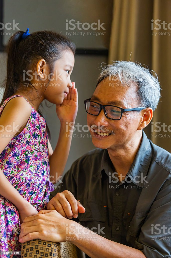 Asian Grandfather and Granddaughter Sharing a Secret stock photo