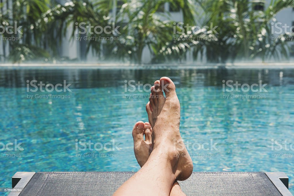 Asian guy lying down on sun lounger at pool side stock photo