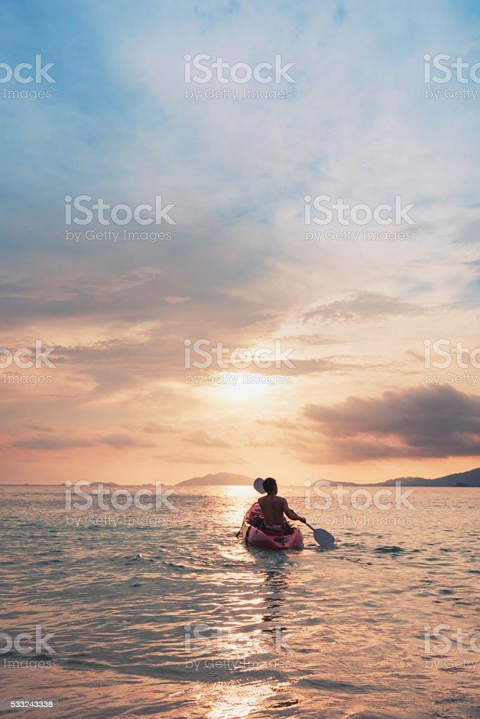 Asian guy on kayak boating to sunset, vintage tone stock photo